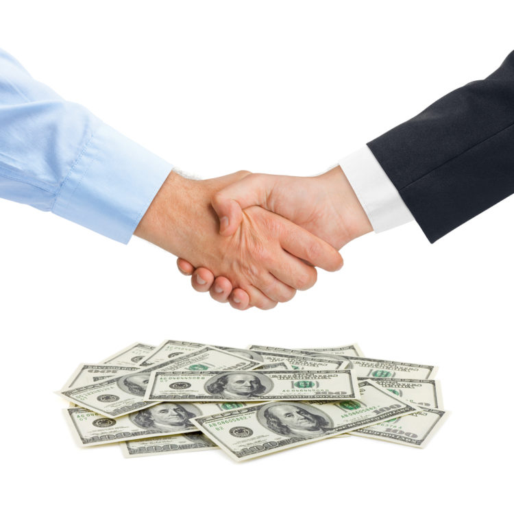 hands shaking above pile of money